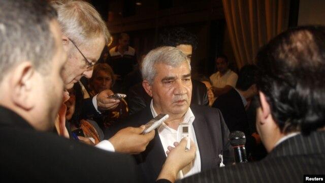 Ông Riad Seif (giữa) nhân vật bất đồng chính kiến hàng đầu của Syria, nói chuyện với các nhà báo tại cuộc họp ở Doha
