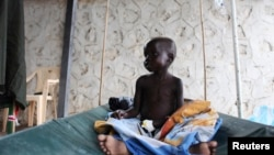 A South Sudanese child suffering from cholera sits on a bed in Juba Teaching Hospital, May 27, 2014. China has pledged $33 million to renovate the hospital.