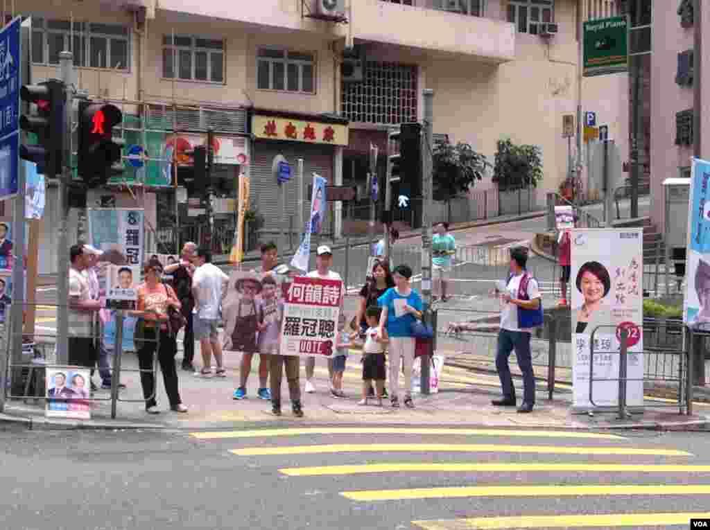 助选义工在路口坚持为各自候选人拉票(美国之音海彦拍摄)
