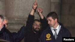"FILE - Ali Charaf Damache, also known by the alias ""Black Flag,"" is accompanied by Irish law enforcement officials as he appears at Waterford District Court to be remanded into custody after being arrested on terrorism charges in Waterford, Ireland, March 13, 2010."
