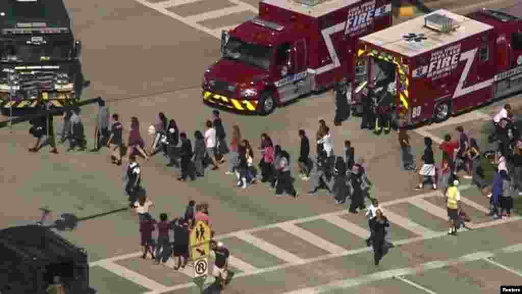 Students are evacuated from Marjory Stoneman Douglas High School during a shooting incident in Parkland, Feb. 14, 2018 in a still image from video.