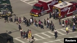 Students are evacuated from Marjory Stoneman Douglas High School during a shooting in Parkland, Florida, Feb. 14, 2018, in this still image from video.