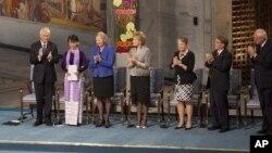 缅甸反对派领导人昂山素季(左2)2012年6月16 日在奥斯陆市政厅发表发表1991年诺贝尔和平奖获奖演说前在讲台上接受挪威诺贝尔奖委员会起立鼓掌