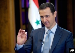 FILE - Syrian President Bashar Assad gives an interview with the BBC in Damascus, Syria. (Photo released by official Syrian news agency SANA)