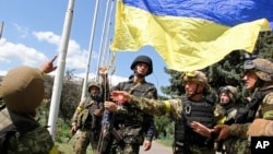 FILE - Ukrainian soldiers and Ukrainian Defense Minister Valery Heletey, third from right, raise a Ukrainian flag in downtown Slovyansk, eastern Ukraine.