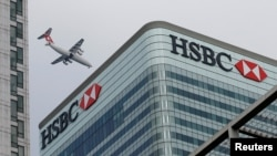 FILE - An aircraft flies past the HSBC headquarters building in the Canary Wharf financial district in east London, Feb. 15, 2015.