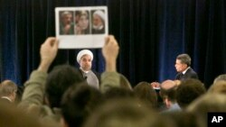 A protester holds up photos of Iranian dissidents under house as Iran's President Hassan Rouhani speaks in New York, Sept. 24, 2014.