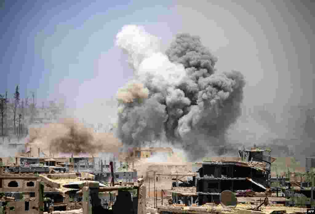 Smoke rises from buildings following a reported airstrike on a rebel-held area in the southern Syrian city of Daraa.