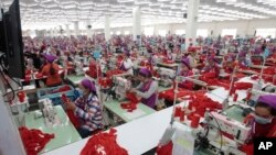 FILE - Garment workers sew clothes in a factory outside Phnom Penh, Cambodia, Aug. 30, 2017. A new government initiative now makes available to them free legal services to help settle disputes with employers. But some see the offer as hollow.