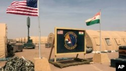 FILE - In this photo taken April 16, 2018, a U.S. and Niger flag are raised side by side at the base camp for air forces and other personnel supporting the construction of Niger Air Base 201 in Agadez, Niger.