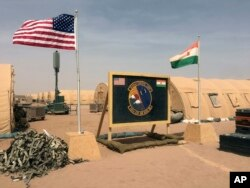 FILE - A U.S. and Niger flag are raised side by side at the base camp for air forces and other personnel supporting the construction of Niger Air Base 201 in Agadez, Niger, April 16, 2018.