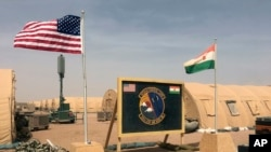 In this photo taken April 16, 2018, a U.S. and Niger flag are raised side by side at the base camp for air forces and other personnel supporting the construction of Niger Air Base 201 in Agadez, Niger.