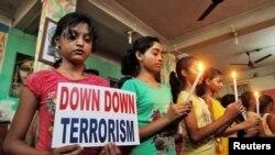 Des élèves en prière de solidarité avec les victimes d'une attaque djihadiste, tiennent des bougies et une plaque dénonçant le terrorisme, à Dhaka, au Bangladesh, 3 juillet 2016. REUTERS / Jayanta Dey