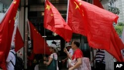 FILE - China supporters march with Chinese national flags during a rally to mark the 18th anniversary of Hong Kong's handover to China, in Hong Kong, July 1, 2015.