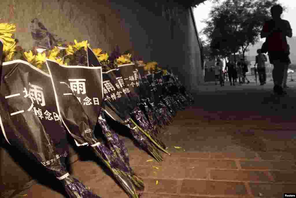 行人从北京广渠门立交桥下哀悼暴雨死难者的菊花旁走过(7月27日)。