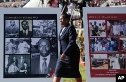 A woman walks past memorial placards for former president Daniel arap Moi, at his state funeral in Nyayo Stadium, in Kenya's capital of Nairobi, Kenya, Feb. 11, 2020.