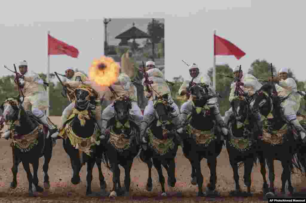 Para pria dengan berkuda menembakkan senjata mereka pada kompetisi nasional 'Fantasia' di El Jadida, Maroko.