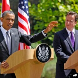 British Prime Minister David Cameron (R) watches U.S. President Barack Obama speak to reporters at Lancaster House in London May 25, 2011