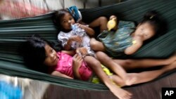 Cambodian children lay in a hummock for sleeping at the sidewalk as swinging by their mother in Phnom Penh, file photo.