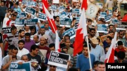 "Anti-government protesters holding Bahraini flags and signs saying ""No To Official Terror"" march during a rally organized by Bahrain's main opposition party Al Wefaq on Budaiya highway west of Manama, August 23, 3013."