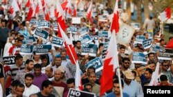 "Anti-government protesters wave Bahraini flags, signs saying ""No to Official Terror"" during rally organized by country's main opposition party Al Wefaq, Manama, Aug. 23, 2013."