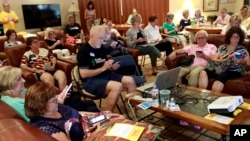 FILE - Community activists learn how to register voters on their phones at a democratic Stand Indivisible AZ monthly meeting in Scottsdale, Ariz., as they strategize about upcoming midterm elections, July 16, 2018.