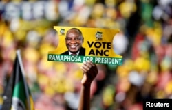 A supporter holds a placard with the face of President of South Africa's governing African National Congress Cyril Ramaphosa, during the party's final rally at Ellis Park Stadium in Johannesburg, South Africa, May 5, 2019.