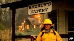 ایک فائر فائٹر علاقے کی تاریخی عمارت کے باہر موجود ہے جب کہ پس منظر میں ایک کیبن میں آگ لگی ہوئی ہے۔