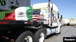 Camiones mexicanos con las banderas de México y Estados Unidos, en la frontera de Laredo.