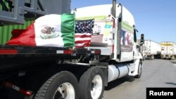 A truck of the Mexican company Olympics bearing Mexican and U.S. flags approaches the border crossing into the U.S.