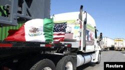 A truck of the Mexican company Olympics bearing Mexican and U.S. flags approaches the border crossing into the U.S., in Laredo, Texas.