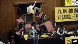 Demonstran Taiwan menumpuk kursi di ruangan parlemen agar tidak dapat dimasuki polisi.