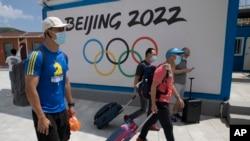 到河北省张家口崇礼的游客走过北京2022冬季奥运会的广告牌。(2020年8月13日)