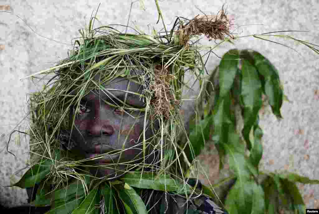 A protester wears grass around his face to obscure his identity during a protest against President Pierre Nkurunziza's decision to run for a third term, in Bujumbura, Burundi.