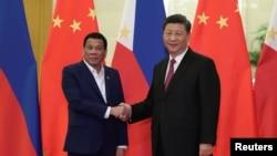 រូបឯកសារ៖ ប្រធានាធីបតីហ្វីលីពីនលោក Rodrigo Duterte ចាប់ដៃជាមួយប្រធានាធិបតីចិនលោក Xi Jinping នៅមុនកិច្ចប្រជុំមួយនៅក្រុងប៉េកាំងកាលបីខែមេសា ឆ្នាំ២០១៩។