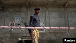 A policeman stands guard at the site of a bomb attack on a Shi'ite mosque in Sargodha, in Pakistan's Punjab province July 19, 2010. At least 15 people were wounded in the suspected suicide attack at a religious centre of minority Shi'ite Muslims in centra