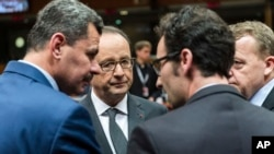 French President Francois Hollande, second from left, speaks with the mayor of Aleppo, Brita Hagi Hasan, left, and Danish Prime Minister Lars Lokke Rasmussen, second from right, during a meeting at an EU Summit in Brussels, Dec. 15, 2016. European Union leaders met to discuss defense, migration, the conflict in Syria and Britain's plans to leave the bloc.