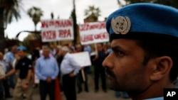 Seorang penjaga perdamaian PBB berjaga-jaga di depan kelompok Yunani dan Turki yang berkumpul di depan hotel tempat perundingan perdamaian berlangsung di Nicosia, Siprus (11/5). (AP/Petros Karadjias)