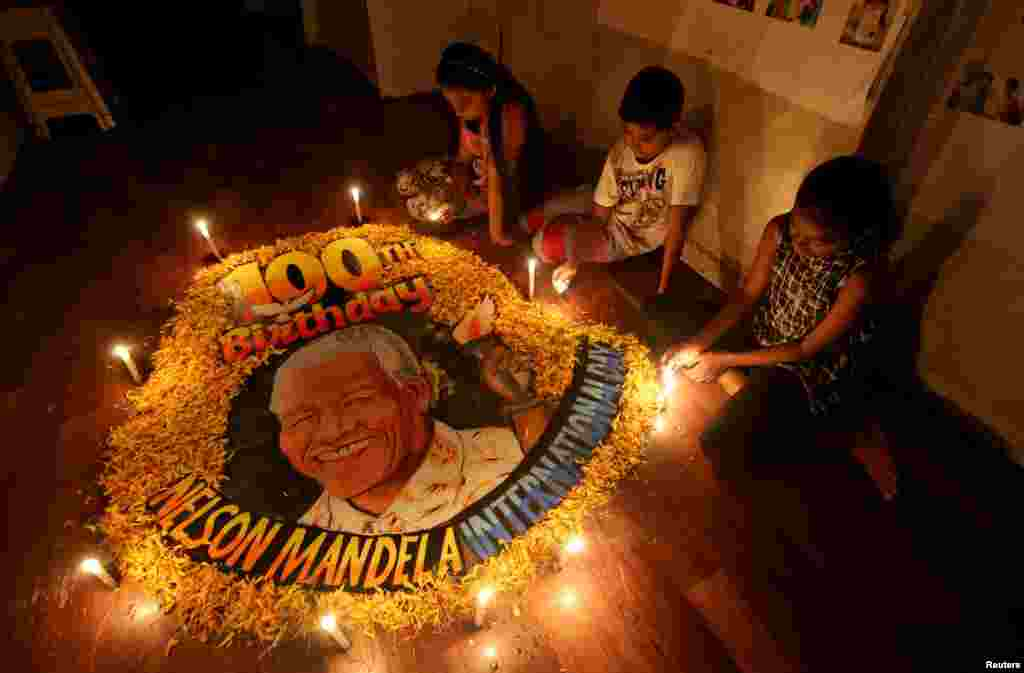 Children light candles beside a painting commemorating South African revolutionary Nelson Mandela's 100th birth anniversary at an art school in Mumbai, India.