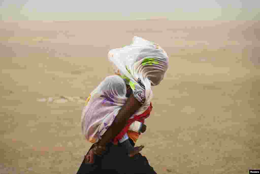 A woman carrying her baby and wrapped with a shawl walks through a sandstorm in Timbuktu, Mali, July 29, 2013.