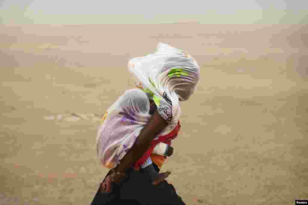 29일 말리 팀북투 지역에서 한 여성이 아기를 안고 모래 폭풍 속을 지나가고 있다.