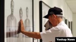 지난 14일 서울 조선일보 미술관에서 열린 광복 70주년 특별 사진전 '마지막 소원'에서 한 이산가족이 헤어진 누나의 모습을 추측해 만든 가상 가족사진을 보며 눈물을 흘리고 있다.