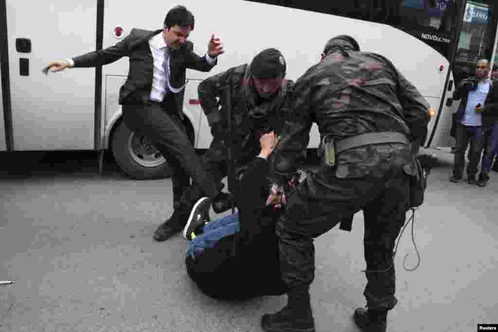 A protester is kicked by Yusuf Yerkel (left), advisor to Turkey's Prime Minister Tayyip Erdogan, as Special Forces police officers detain him during a protest against Erdogan's visit to Soma, where the mining disaster occurred, western province of Manisa, Turkey, May 14, 2014.