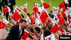 习近平访问韩国时在首尔的欢迎仪式上,儿童们挥舞中国和韩国国旗。