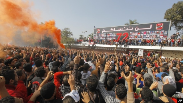Egyptian soccer fans of Al-Ahly football club celebrate in front of their club premises in Cairo, Egypt, January 26, 2013.