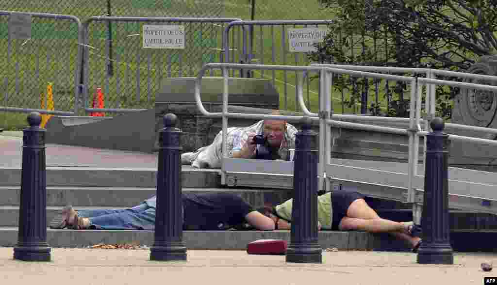 People take cover as gun shots were heard at the U.S. Capitol in Washington.