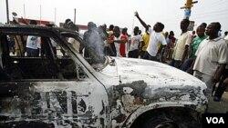 Para mahasiswa pendukung Gbagbo membakar kendaraan PBB dalam demonstrasi di Abidjan, Kamis 13 Januari 2011.