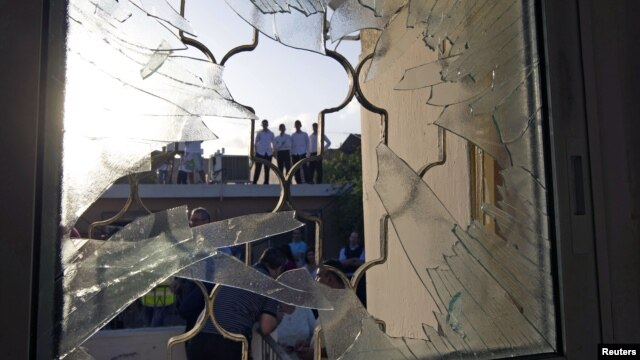 Israelis are seen through a window damaged after a rocket fired from the Gaza Strip landed in the southern town of Ofakim, November 18, 2012.