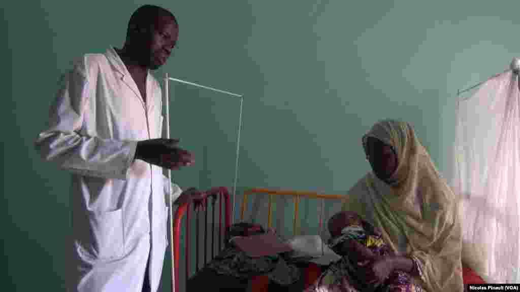 Le docteur Moustapha Saley s'entretient avec la mère d'un enfant souffrant de malnutrition aiguë au centre régional de santé mère enfant de Diffa, Niger, le 18 avril 2017 (VOA/Nicolas Pinault)