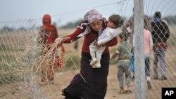 Một phụ nữ Syria đi thu gom cành khô để đốt lửa ở trại tị nạn gần biên giới với Thổ Nhĩ Kỳ. Số người Syria tị nạn được nhận vào Hoa Kỳ dự kiến lên tới 1.800 người tính đến cuối tháng 10.